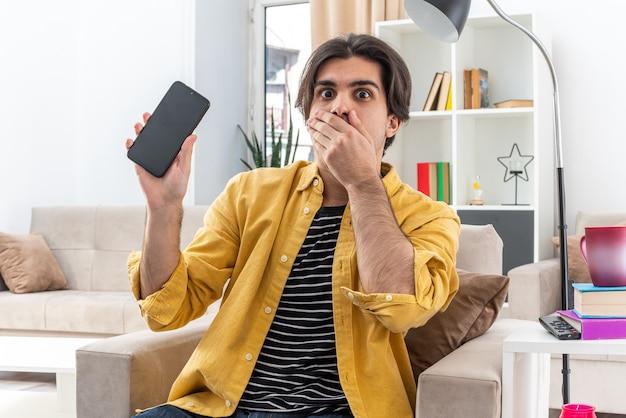 Młody człowiek w zwykłych ubraniach trzymający smartfona patrzący na szok, zakrywający usta ręką siedzącą na krześle w jasnym salonie