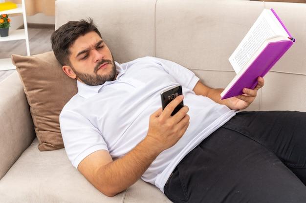 Młody człowiek w zwykłych ubraniach z książką trzymającą smartfona, patrząc na to z poważną twarzą, spędzając weekend w domu leżąc na kanapie w jasnym salonie