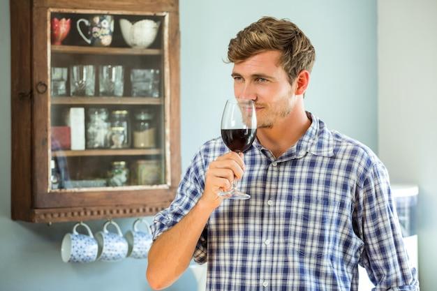 Młody człowiek wącha kieliszek czerwonego wina