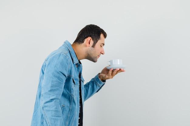 Młody człowiek wąchający aromatyczną herbatę w koszulce, kurtce i wyglądający na zachwyconego. .