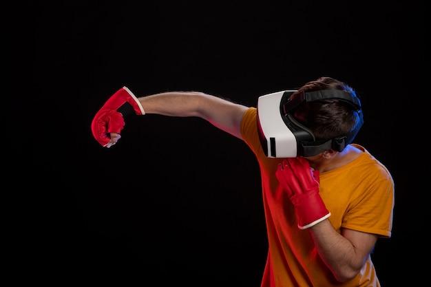 Młody człowiek walczy w wirtualnej rzeczywistości z rękawiczkami mma na czarnej powierzchni