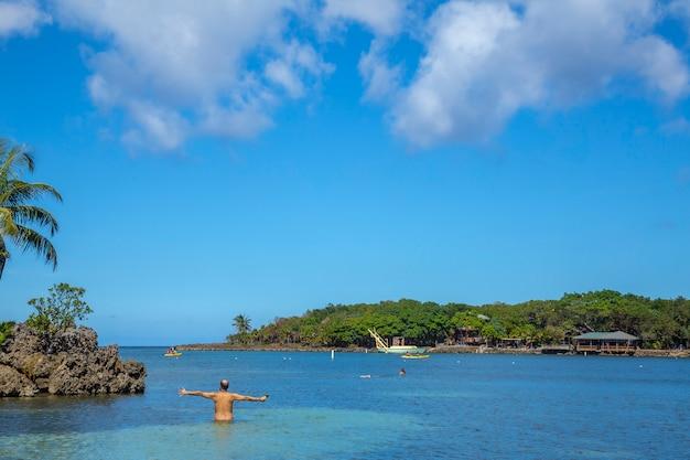 Młody człowiek wchodzący na morze karaibskie w west end beach na wyspie roatan. honduras