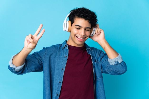 Młody człowiek wenezueli na białym tle na niebieskiej ścianie słuchania muzyki i śpiewu