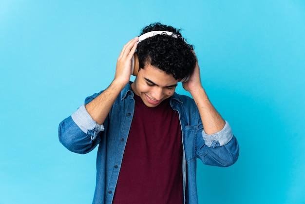 Młody człowiek wenezueli na białym tle na niebieskiej ścianie słuchania muzyki