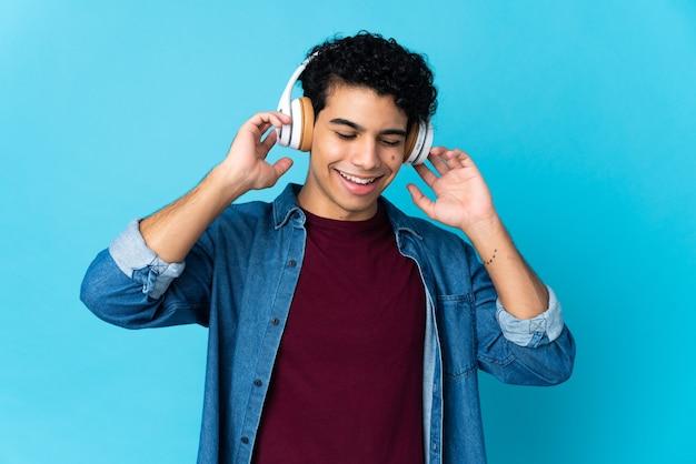 Młody człowiek wenezueli na białym tle na niebieskim tle słuchania muzyki i śpiewu