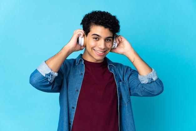 Młody człowiek wenezueli na białym tle na niebieskim tle słuchania muzyki