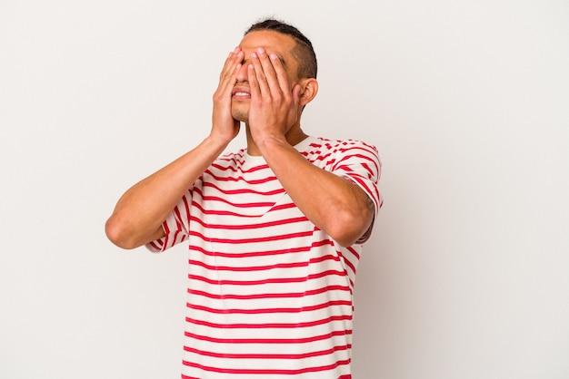 Młody człowiek wenezuelski na białym tle boi się zasłaniając oczy rękami.