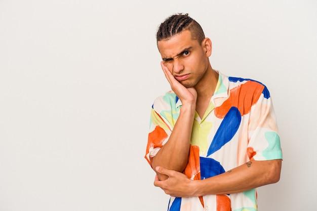 Młody człowiek wenezuelski na białym tle, który czuje się smutny i zamyślony, patrząc na miejsce.