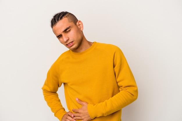 Młody człowiek wenezuelski na białym tle na białej ścianie o ból wątroby, ból brzucha.