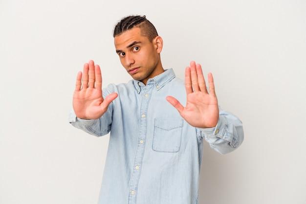 Młody człowiek wenezuelski na białym tle na białym tle stojący z wyciągniętą ręką pokazując znak stop, uniemożliwiając.