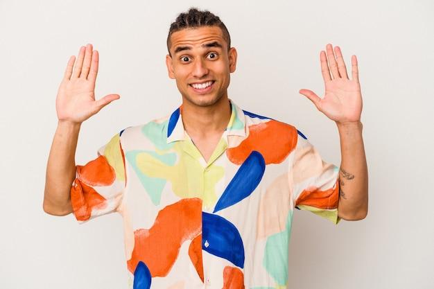 Młody człowiek wenezuelski na białym tle odbiera miłą niespodziankę, podekscytowany i podnosząc ręce.