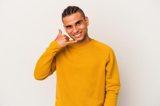 Młody człowiek wenezuelski na białym tle pokazując gest połączenia z telefonu komórkowego palcami.