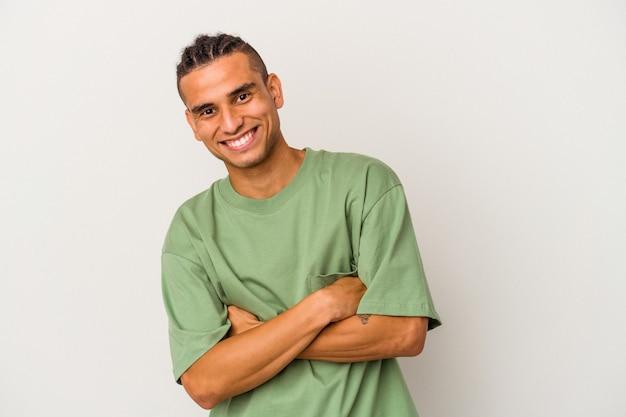 Młody człowiek wenezuelski na białym tle śmiejąc się i zabawę.