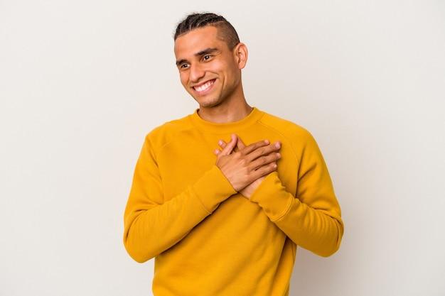 Młody człowiek wenezuelski na białym tle śmiejąc się trzymając ręce na sercu, pojęcie szczęścia.