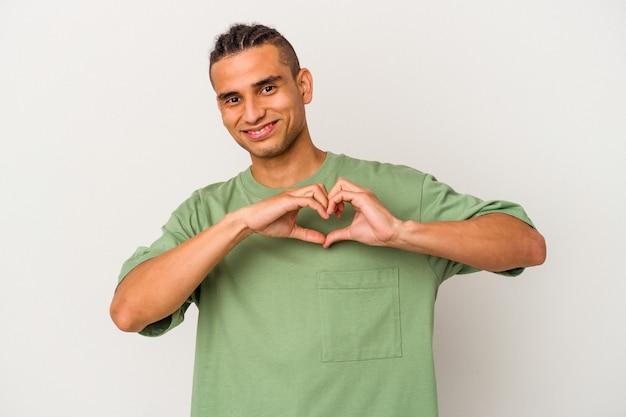 Młody człowiek wenezuelski na białym tle uśmiechający się i pokazujący kształt serca rękami.