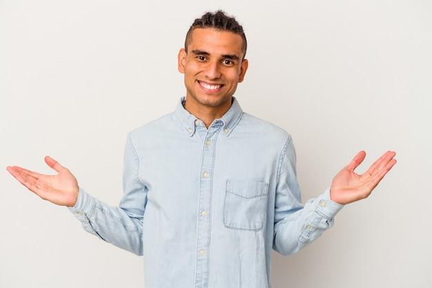 Młody człowiek wenezuelski na białym tle wątpiąc i wzruszając ramionami w geście przesłuchania.