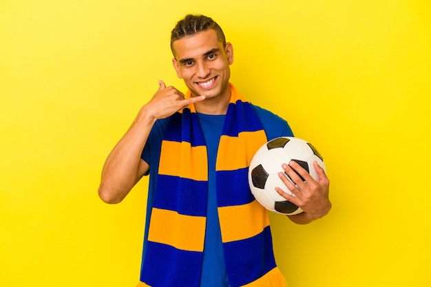 Młody człowiek wenezuelski oglądanie piłki nożnej na białym tle na żółtym tle pokazując gest połączenia z telefonu komórkowego palcami.