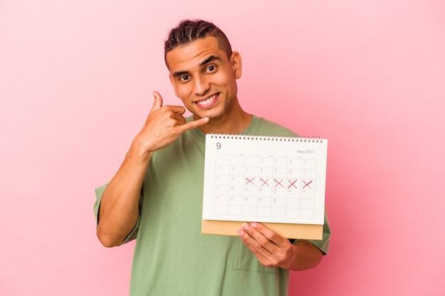 Młody człowiek wenezuelski trzyma kalendarz na białym tle na różowej ścianie pokazujący gest połączenia z telefonem komórkowym palcami.