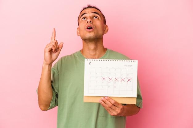 Młody człowiek wenezuelski trzyma kalendarz na białym tle na różowej ścianie, wskazując do góry z otwartymi ustami.