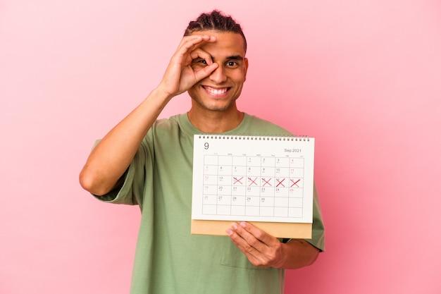 Młody człowiek wenezuelski trzyma kalendarz na białym tle na różowym tle podekscytowany, zachowując ok gest na oko.
