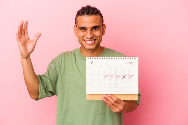 Młody człowiek wenezuelski trzymający kalendarz na białym tle na różowym tle otrzymujący miłą niespodziankę, podekscytowany i podnoszący ręce.
