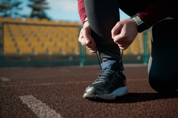 Młody człowiek wiązanie sznurówek przed joggingiem na stadionie