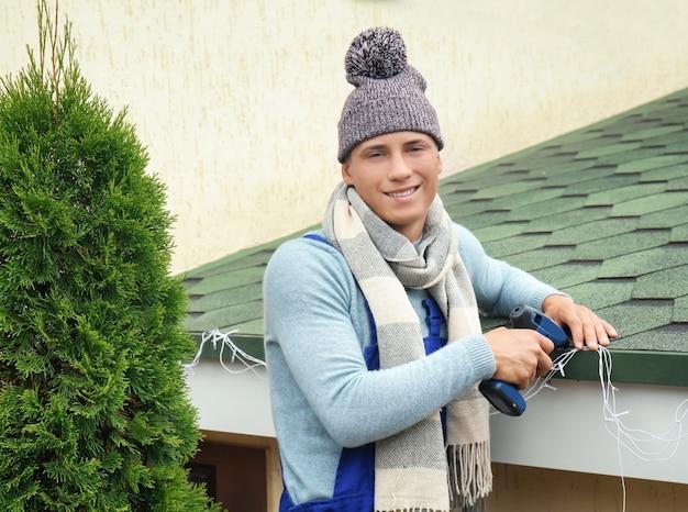 Młody człowiek wiszący świąteczne lampki na dachu domu