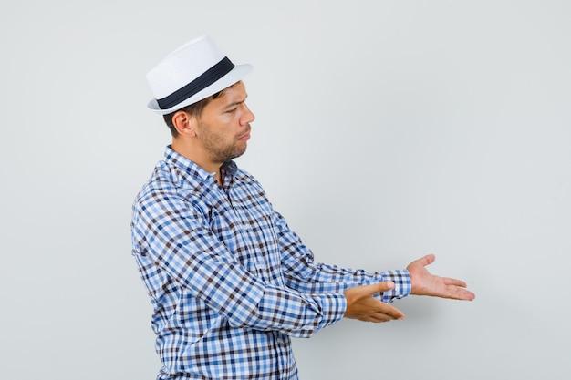 Młody człowiek wita lub pokazuje coś w koszuli w kratę