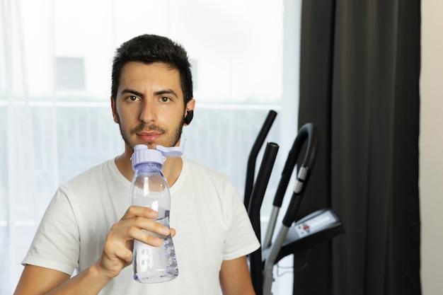 Młody człowiek woda pitna w pomieszczeniu