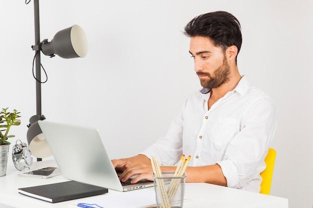 Młody człowiek wpisując na laptopie