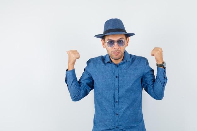 Młody człowiek wskazując kciuki w niebieską koszulę, kapelusz i wyglądający pewnie. przedni widok.