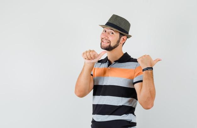 Młody człowiek wskazując kciuki z powrotem w t-shirt, kapelusz i wesoły wyglądający