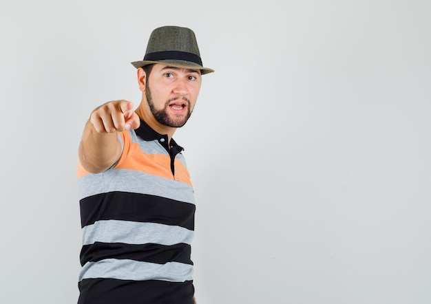 Młody człowiek, wskazując na aparat do oskarżenia w t-shirt, kapelusz i patrząc pewnie. przedni widok.