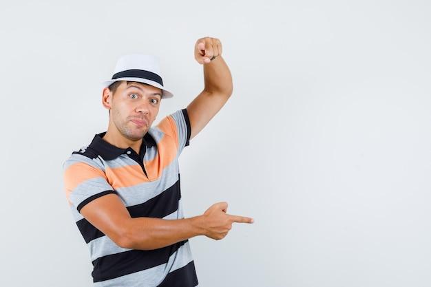 Młody człowiek, wskazując na bok i aparat w koszulce i kapeluszu i patrząc zaciekawiony