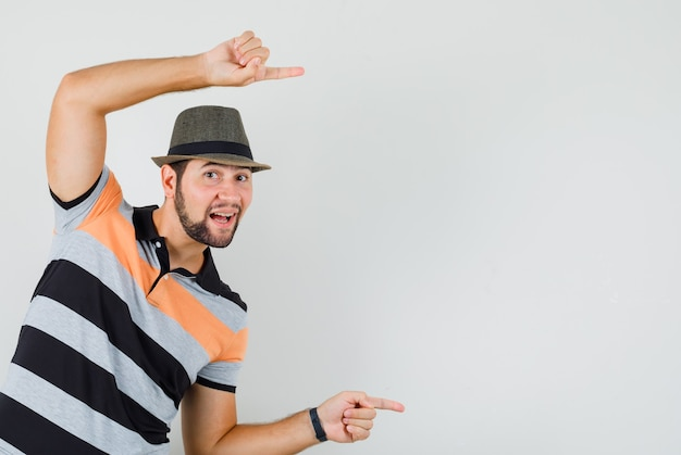Młody człowiek, wskazując na bok w koszulce, kapeluszu i patrząc zadowolony.
