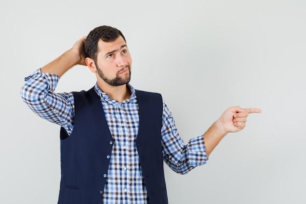 Młody człowiek, wskazując na bok w koszuli, kamizelce i zamyślony.