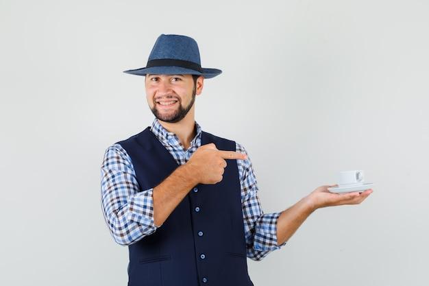 Młody człowiek, wskazując na filiżankę herbaty w koszulę, kamizelkę, kapelusz i patrząc wesoło, widok z przodu.