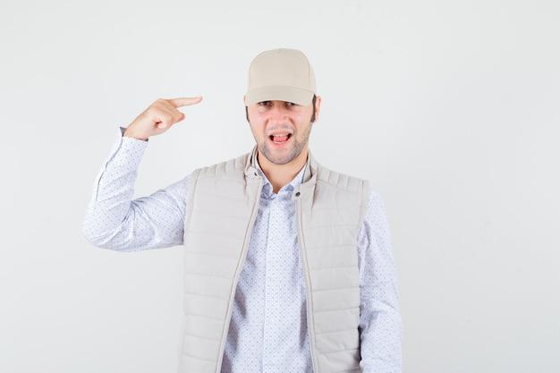 Młody człowiek, wskazując na jego czapkę w koszuli, kurtce bez rękawów, czapce i patrząc optymistycznie, widok z przodu.