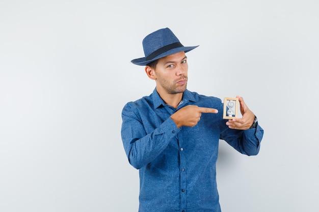 Młody człowiek, wskazując na klepsydrę w niebieskiej koszuli, kapeluszu i patrząc rozsądnie, widok z przodu.
