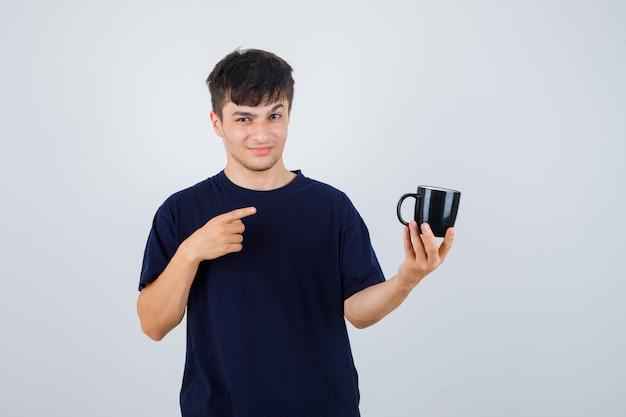 Młody człowiek, wskazując na kubek w czarnej koszulce i patrząc niezdecydowany, widok z przodu.
