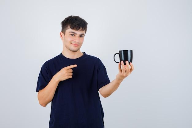 Młody człowiek, wskazując na kubek w czarnej koszulce i patrząc pewnie, widok z przodu.