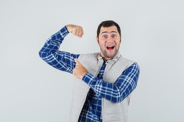 Młody człowiek, wskazując na mięśnie ramion w koszuli, kurtce bez rękawów i patrząc pozytywnie, widok z przodu.