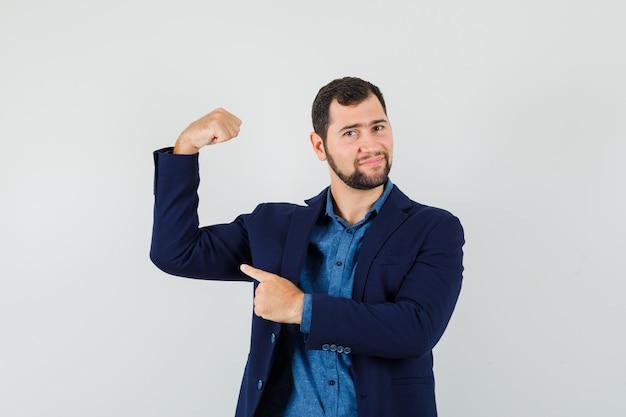 Młody człowiek, wskazując na mięśnie ramion w koszuli, kurtce i patrząc potężny. przedni widok.