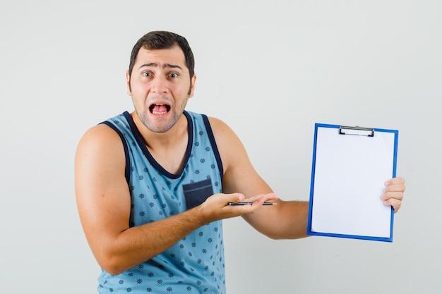 Młody człowiek, wskazując na schowek w niebieskim podkoszulku i patrząc zaniepokojony.