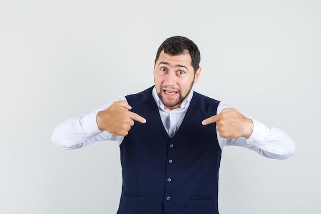 Młody człowiek, wskazując na siebie w koszuli, kamizelce i wyglądający na zdezorientowanego