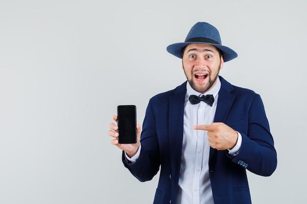 Młody człowiek, wskazując na telefon komórkowy w garniturze, kapeluszu i patrząc szczęśliwy. przedni widok.