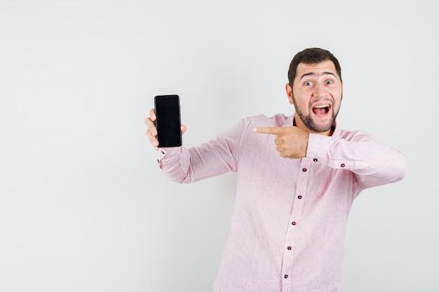 Młody człowiek, wskazując na telefon komórkowy w różowej koszuli i patrząc radośnie