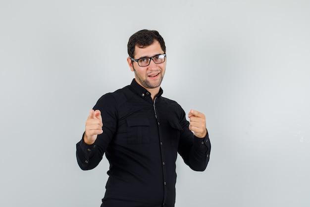 Młody człowiek wskazując palcami na aparat w czarnej koszuli, okularach i wesoło wyglądający