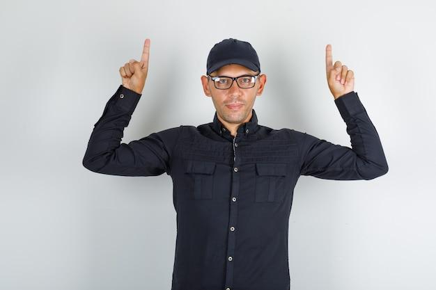Młody człowiek wskazując palcami w czarnej koszuli z czapką