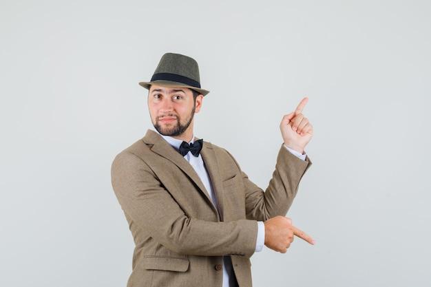Młody człowiek, wskazując palcami w dół iw górę, w garniturze, kapeluszu i wyglądający rozsądnie. przedni widok.